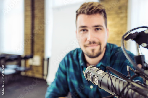 Valokuva  Attractive Young Man speaking Into Microphone
