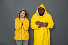 Half Length Of Young Interracial Couple Wearing Yellow Raincoats Against Gray Background