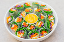 Vegan Food Concept. Tasty Green Spring Rolls Made Of Rice Paper And Spinach, Filled With Fresh Chopped Vegetables. Small Plate With Yellow Curry Sauce In Middle