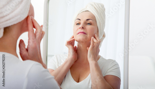 Canvastavla  Forty years old woman looking at wrinkles in mirror