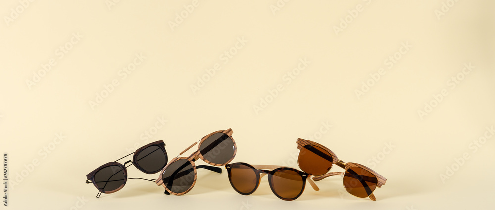 Fototapeta Wooden sunglasses of different design on yellow background. Copy space. Sunglasses sale concept. For banner optic shop