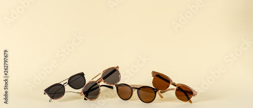 Wooden sunglasses of different design on yellow background Fototapet