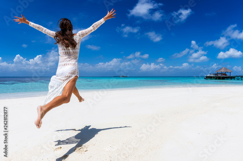 Fotografie, Obraz  Glückliche Frau in weißem Sommerkleid läuft an einem tropischen Paradies Strand