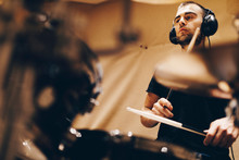 Positive Handsome Male With Headphones Playing On Drums In Studio