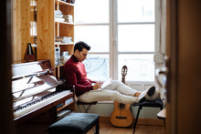 Songwriter Man Sitting By A Window Composing Music In A Notebook