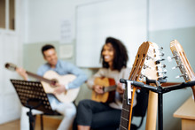 Young Man And Woman Playing Guitar During Rehearsal In Recording Studio.
