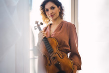 Pregnant Woman Next To A Window With Her Violin