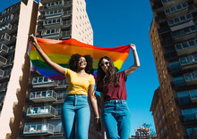 Lesbian Couple Celebrating With LGBT Flag On Gay Pride Day