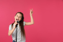 Cute Girl Singing In Microphone On Color Background. Space For Text