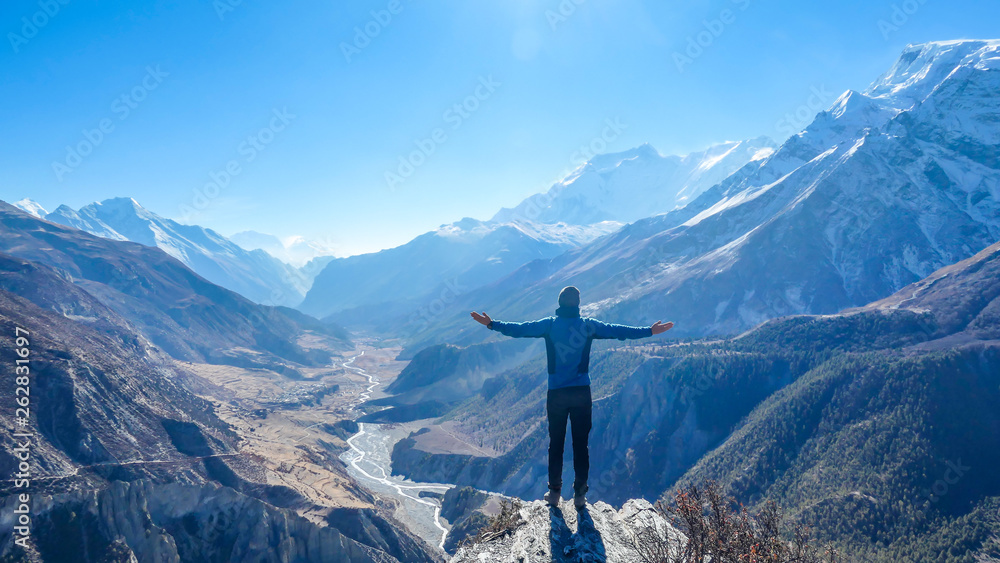 Fototapety, obrazy: Man wearing a beanie and blue jumper, spreads his arms wide, breathing deeply the fresh mountain air. His gesture represents freedom and happiness. Below a long valley stretches in Himalayas.