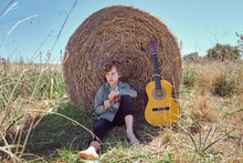 Cute Boy Playing Acoustic Guitar And Singing While Sitting Near Huge Roll Of Dry Hay On Sunny Day In Countryside