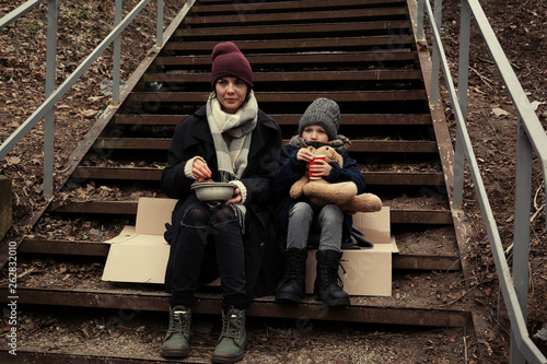 Valokuva  Poor mother and daughter with bread sitting on stairs outdoors