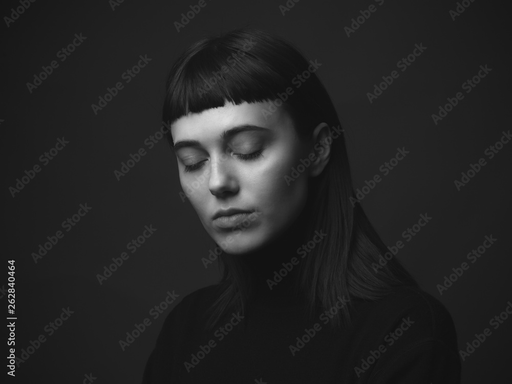 Fototapeta Attractive young woman with closed eyes in studio. Black and white