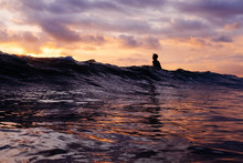 Person Swimming In The Waves During Sunset On A Warm Summer Day.