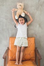 Asian Kid With Her Teddy Bear On The Old Chair
