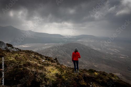Photo sur Toile Marron chocolat une femme en haut d'une montagne devant un paysage grandioses sous un ciel menaçant