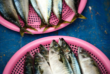 Fish Heads And Tails In Pink Baskets On A Blue Table