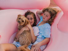 Two Girls Laying With Their Dog In Inflatable Flamingo