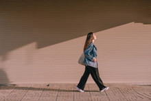 Young Asian Woman Walking On Street In The Sunny Day.