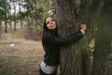 Young Woman Hugging Tree In Th...