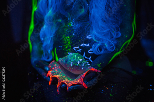 Photo  seashell in the neon light in the hands of a pregnant girl
