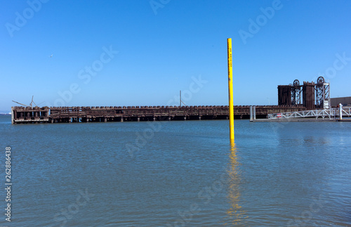 Fotografie, Obraz  yellow pole and reflection  in bay with pier and blue sky