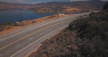 Shown From Above, Team Of Deputy Sheriffs Ride Past Castaic Lake In Castaic.  This Is Aerial Drone Footage Caught Overseeing This Team.