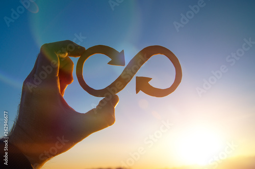 Fotografia  A symbol of infinity in the hand of a man against the sky and the glare of the sun, business concept idea