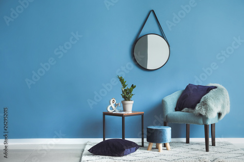 Beautiful interior with comfortable armchair, table and mirror Fototapete