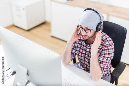 Photo  Creative man with headphones listening to music on his computer.
