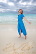 woman in a long blue dress next to the numbers year 2020 in the sand