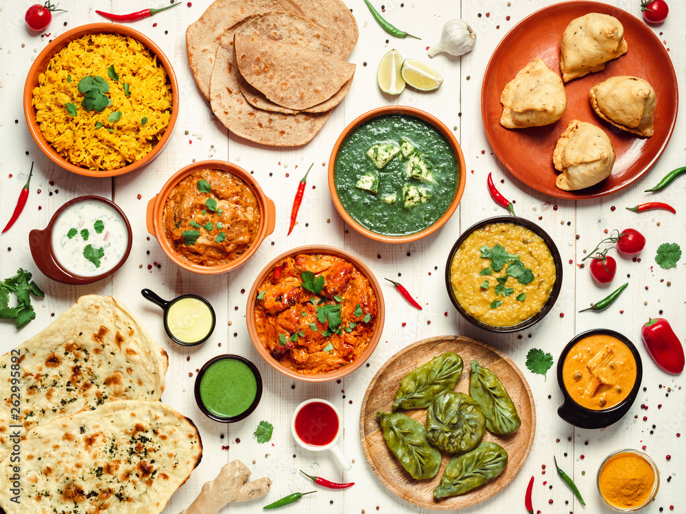 Fototapeta Indian cuisine dishes: tikka masala, dal, paneer, samosa, chapati, chutney, spices. Indian food on white wooden background. Assortment indian meal top view or flat lay.