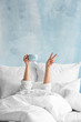 canvas print picture - Young woman with cup of hot beverage showing victory gesture in bed