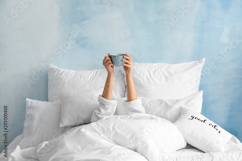 Young woman with cup of hot beverage lying in bed
