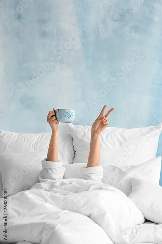 Obraz Young woman with cup of hot beverage showing victory gesture in bed - fototapety do salonu