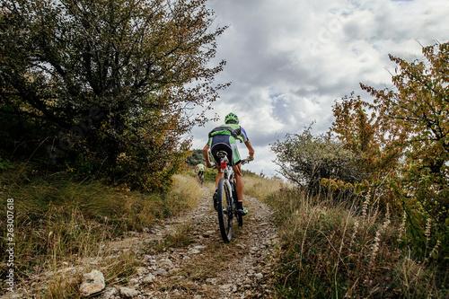 Obraz na płótnie two athletes cyclists on mountain bike riding uphill on mountain trail