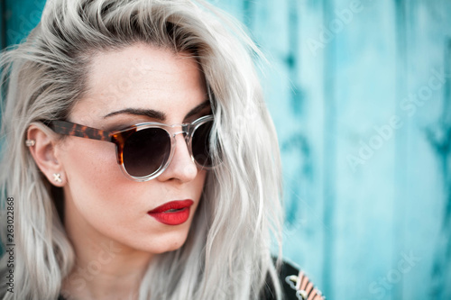 blond woman with glasses blue background Tablou Canvas