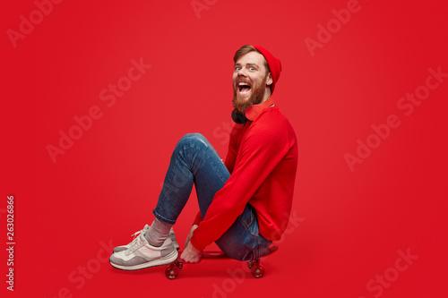 Funny hipster sitting on skateboard Fototapet