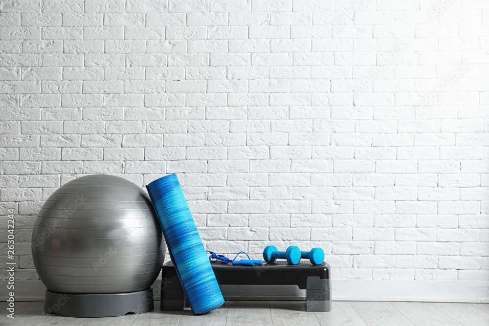 Fototapety, obrazy: Set of fitness inventory on floor near brick wall. Space for text