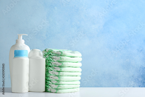 Fotografiet  Stack of diapers and toiletries on table against color background, space for text