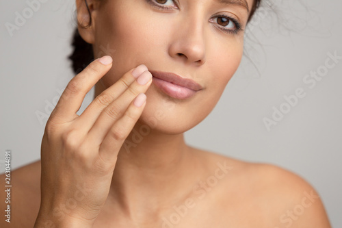 Natural beauty. Woman applying balsam, touching lips Wallpaper Mural