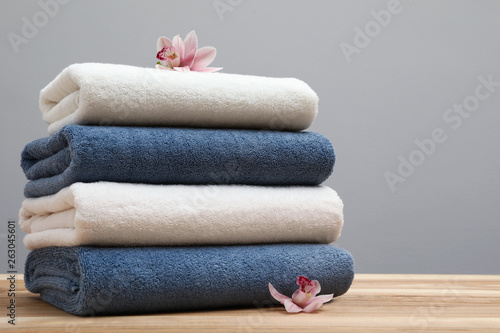 Photo  Stack of fresh towels with flowers on table. Space for text