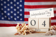 Composition With Wooden Calendar And Card On Sand Against USA Flag, Space For Text. Happy Independence Day