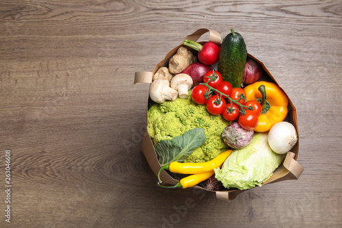 Paper bag full of fresh vegetables on wooden background, top view. Space for text