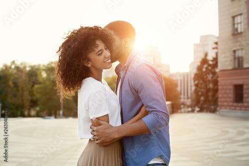 Foto  African-american boyfriend whispering words of love to girlfriend