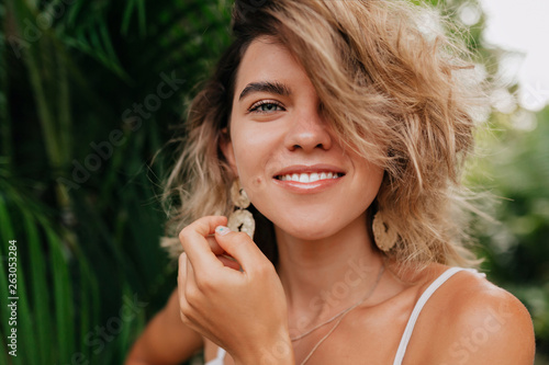 European happy woman with white teeth and green eyes wearing earnings looking at camera with wonderful smile