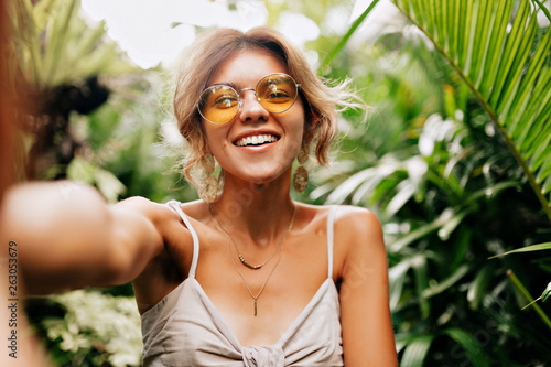 Deurstickers Ontspanning Young caucasian pretty woman wearing yellow round glasses making selfie with happy smile on background exotic plants