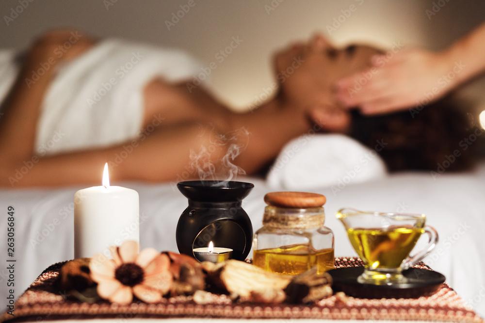 Fototapeta African woman having face massage, relaxing in spa salon