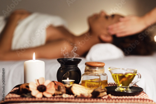 Fotomural African woman having face massage, relaxing in spa salon