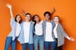 canvas print picture - Students having fun over orange studio background